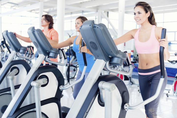 People training at the gym with Elliptical trainer